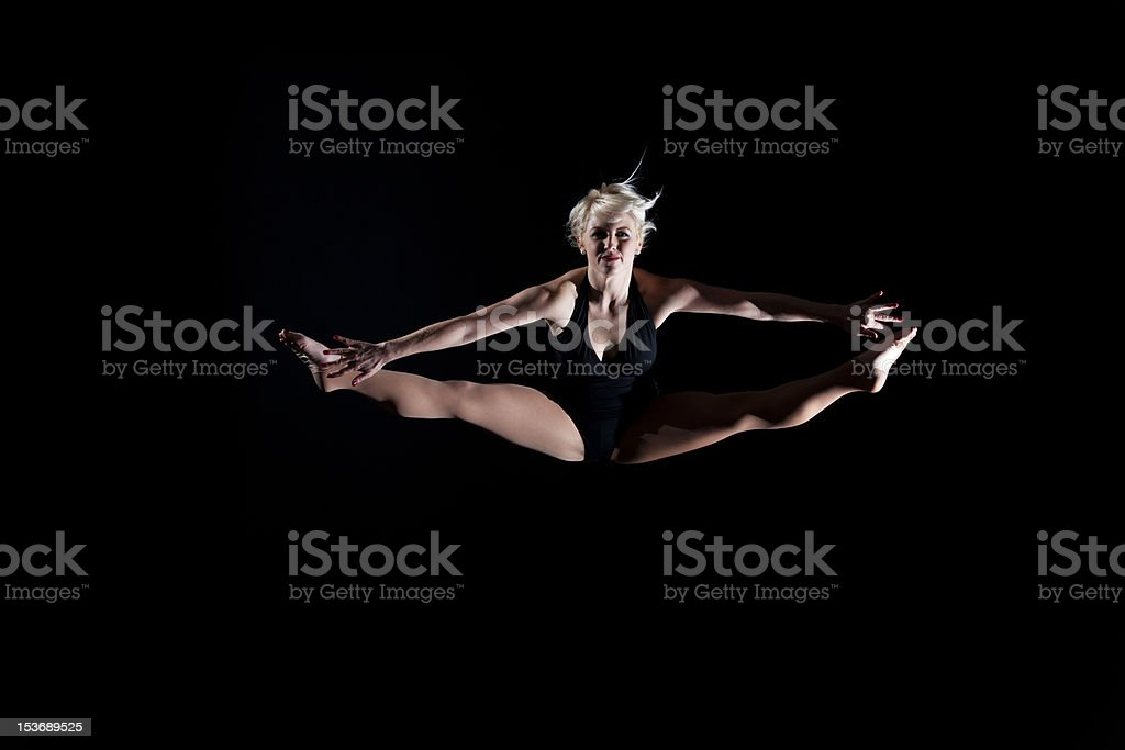 Beautiful young woman gymnast leaping doing splits in air royalty-free stock photo