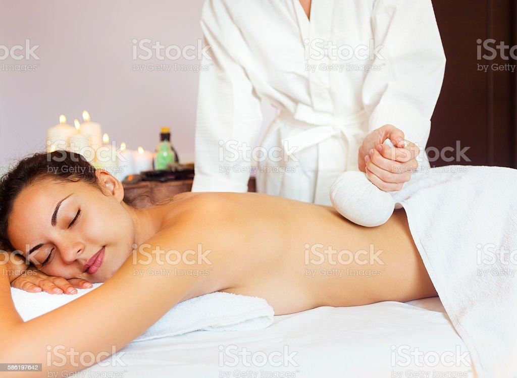 Beautiful young woman having back massage with pouch of rice stock photo