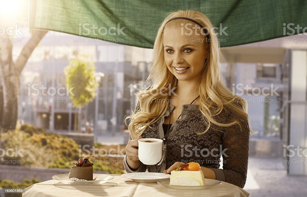 Beautiful young woman having cake outdoors royalty-free stock photo