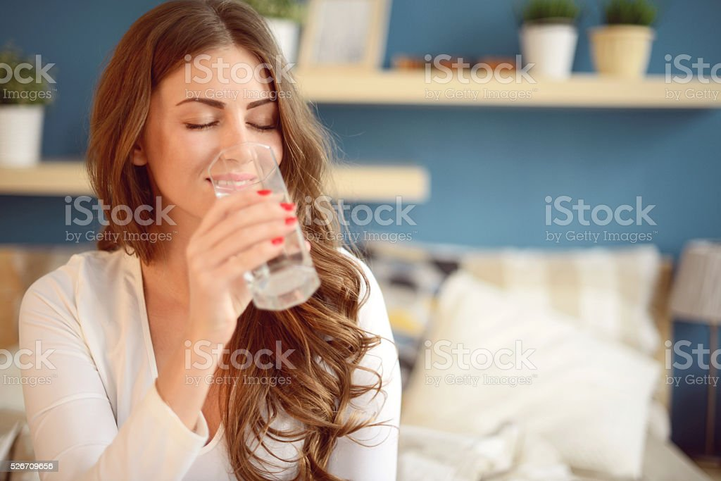 beautiful young woman holding a glass of water stock photo