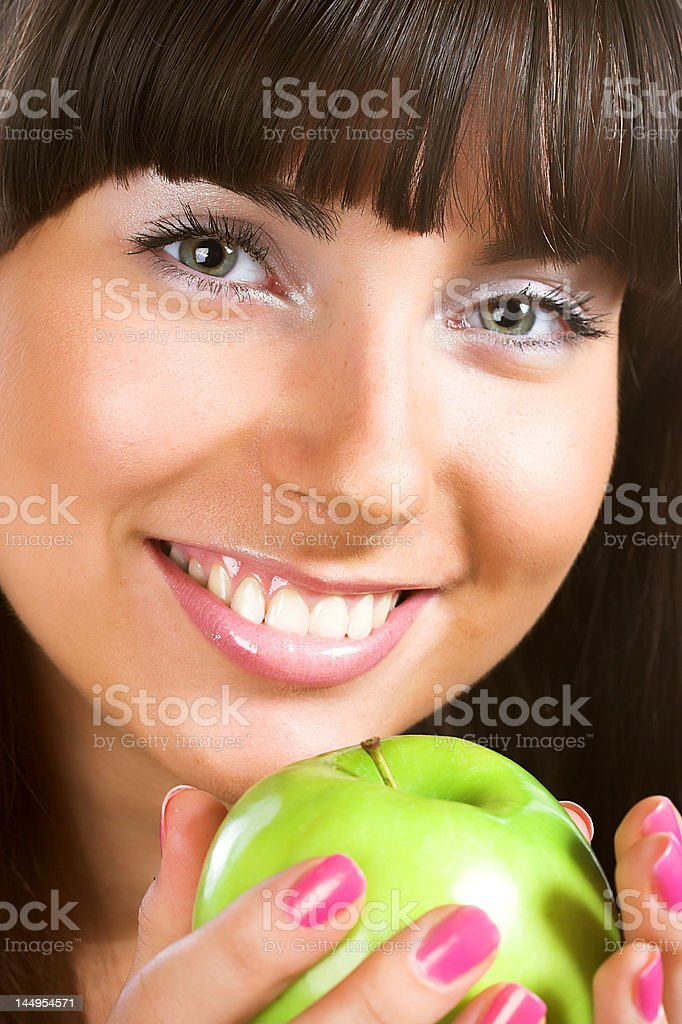 Beautiful young woman holding a green apple royalty-free stock photo