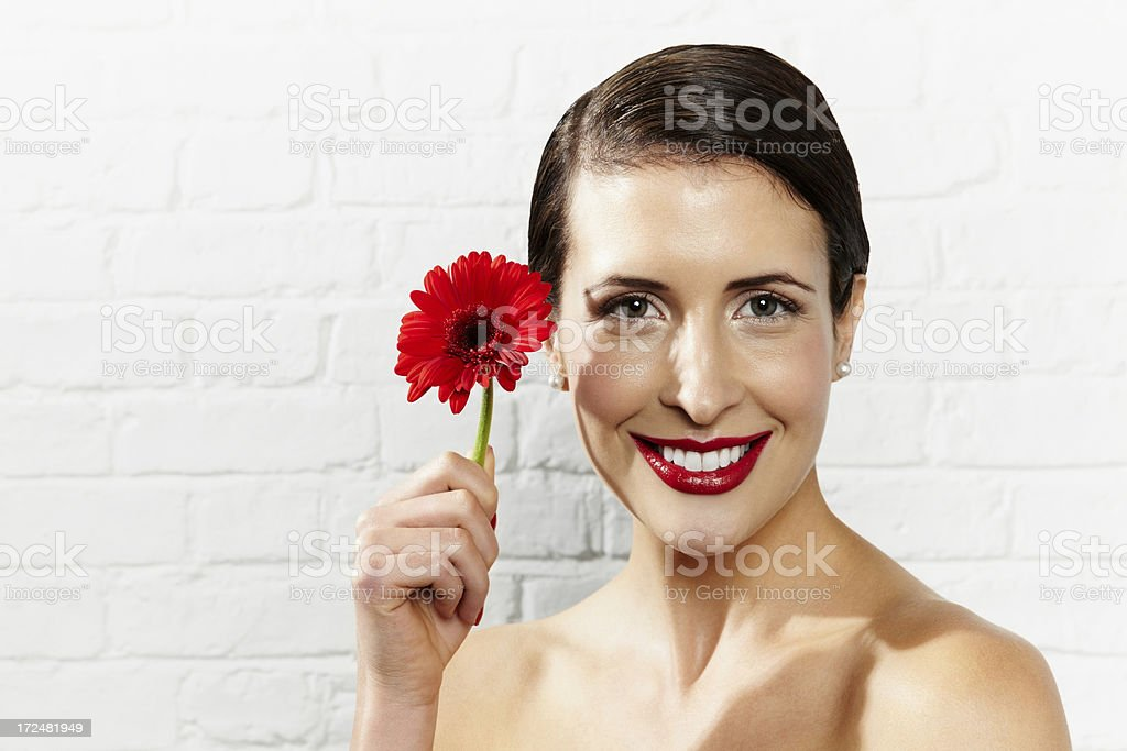 Beautiful young woman holding a red flower royalty-free stock photo