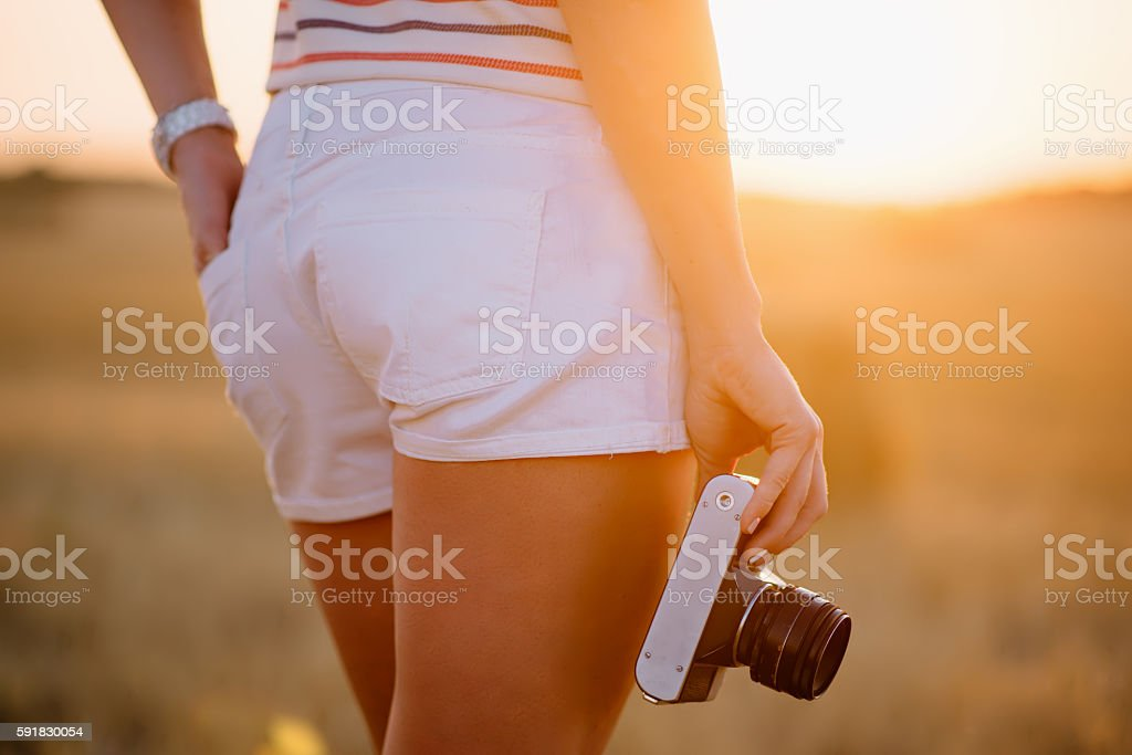beautiful young woman holding a vintage camera at hip level stock photo