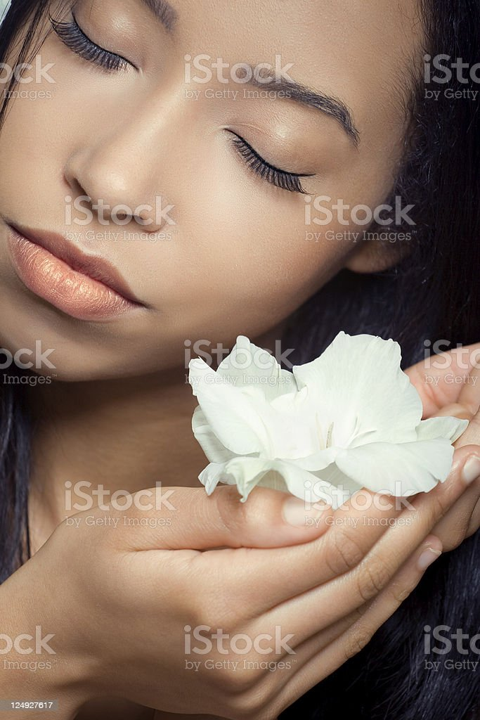 Beautiful young woman holding a white flower near her face royalty-free stock photo