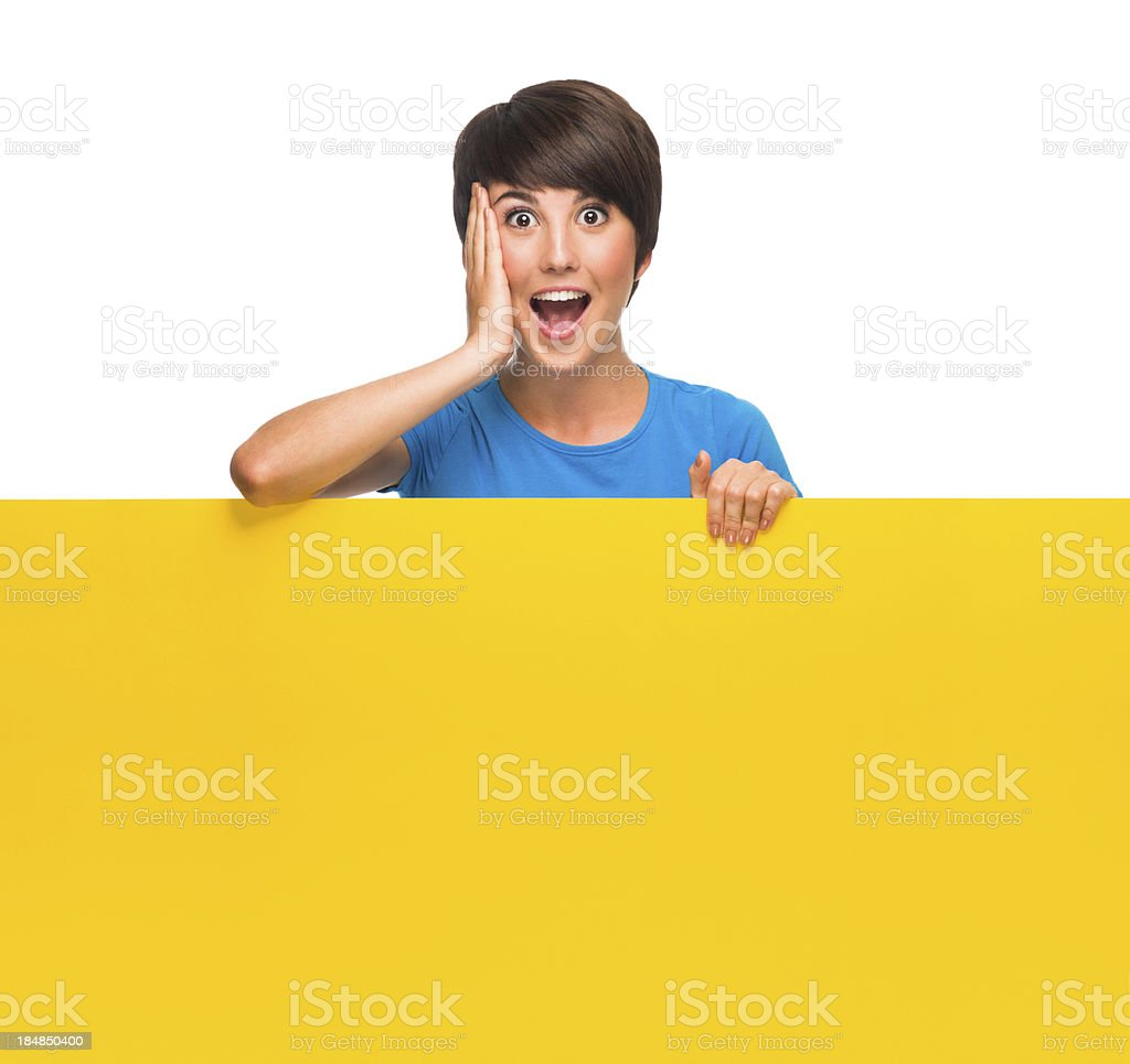 Beautiful young woman holding a yellow sign royalty-free stock photo