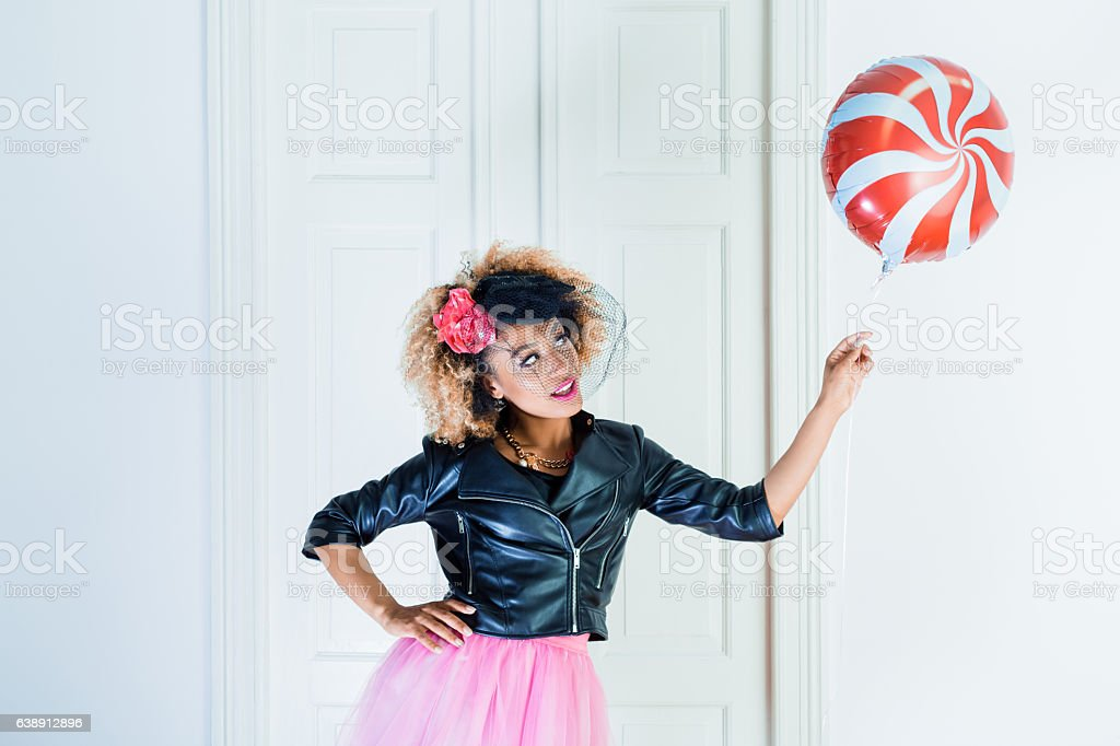 Beautiful young woman holding balloon indoors stock photo