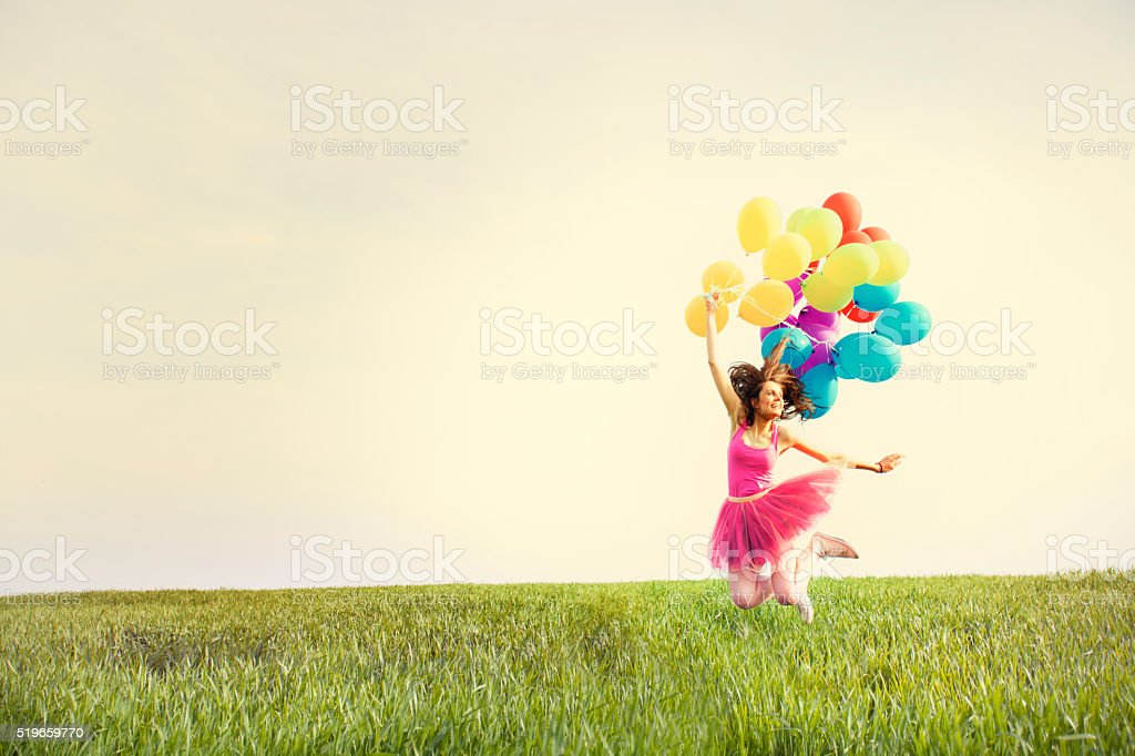 Beautiful young woman holding balloons and jumping on the field stock photo