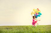 Beautiful young woman holding balloons and jumping on the field