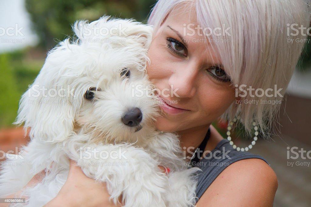 Beautiful young woman holding cute Coton de Tulear dog stock photo