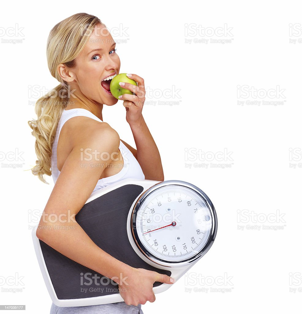 Beautiful young woman holding measuring instrument and eating an apple stock photo