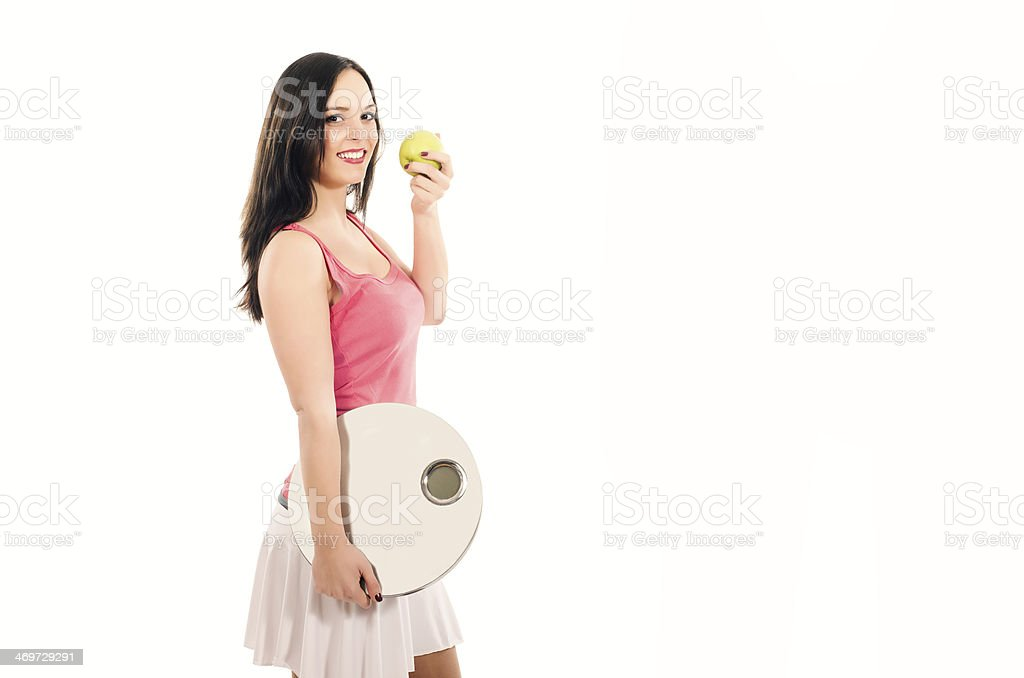 Beautiful young woman holding measuring instrument and eating an apple royalty-free stock photo