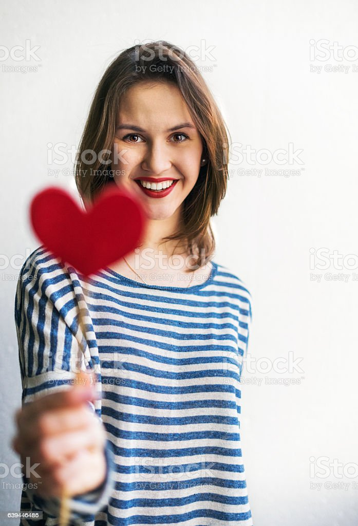 Beautiful young woman holding paper heart stock photo