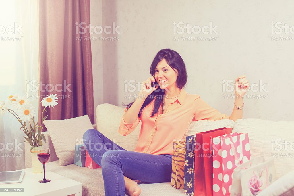 Beautiful young woman holding tablet with shopping bags on sofa stock photo