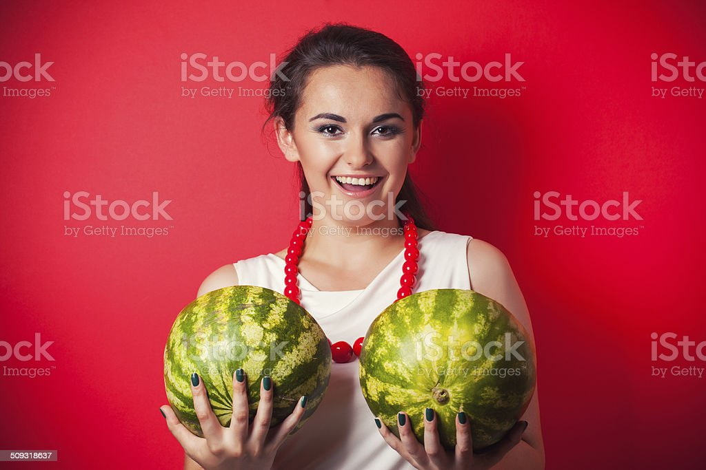 beautiful young woman holding watermelon against red background stock photo