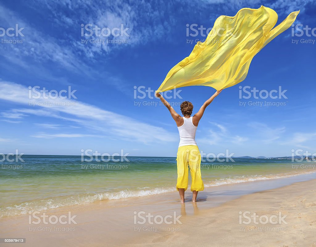 Beautiful young woman holding yellow fabric on wind stock photo