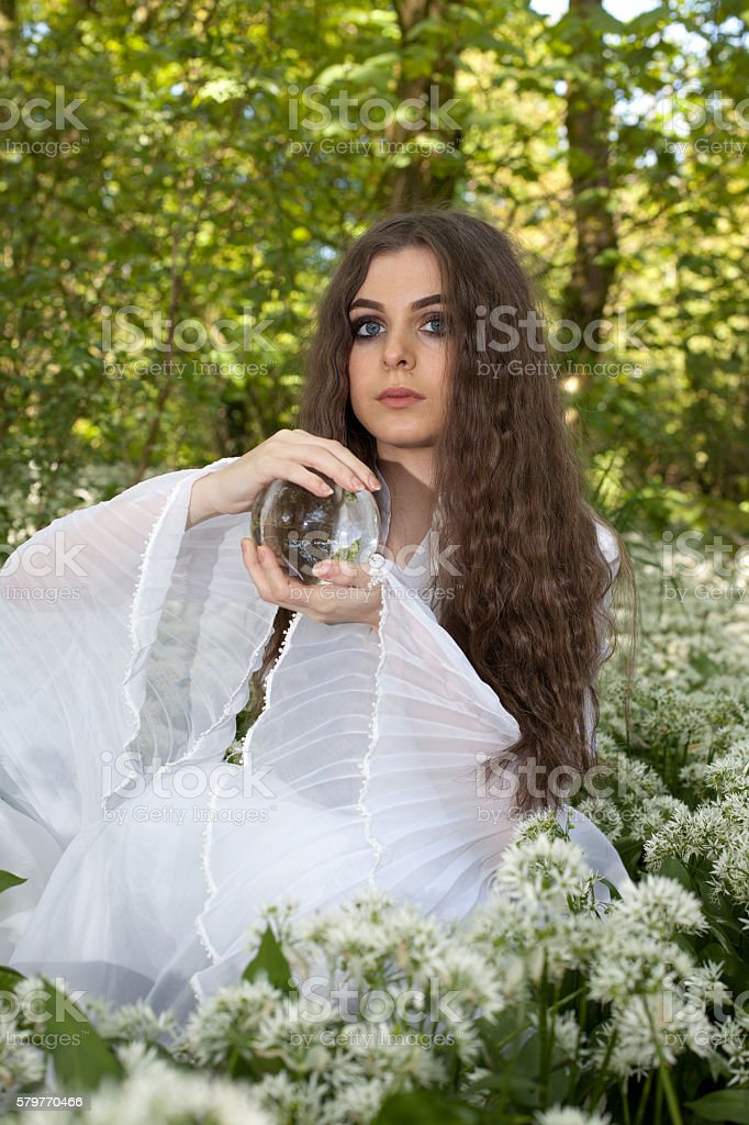 Beautiful young woman in a forest holding a crystal ball stock photo