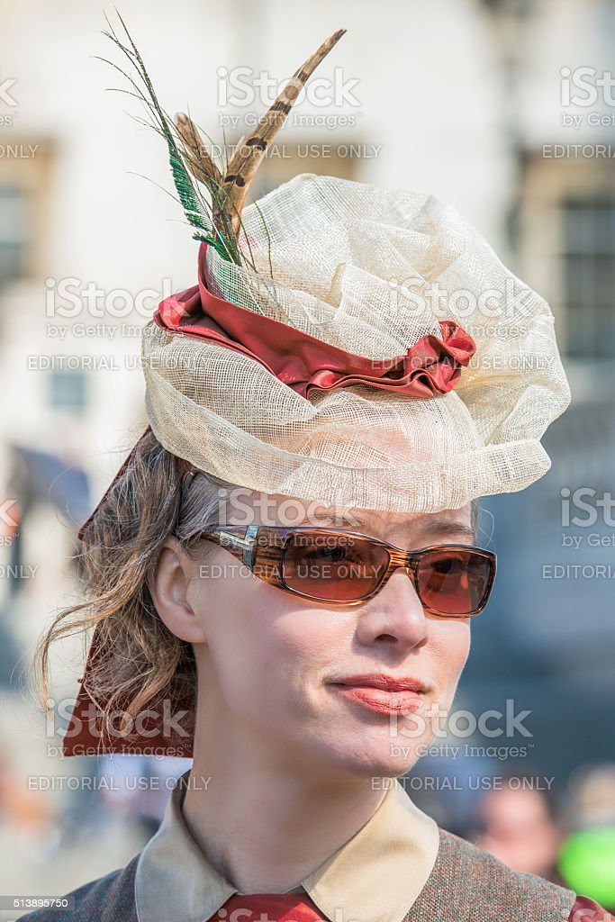 Beautiful young woman in a gorgeous feather hat and sunglasses stock photo