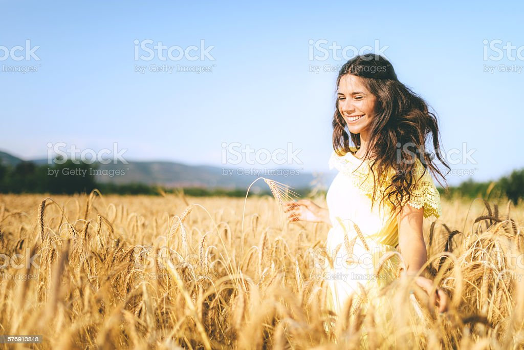 beautiful young woman in a wheat golden field stock photo