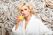 beautiful young woman in a white robe drinking orange juice