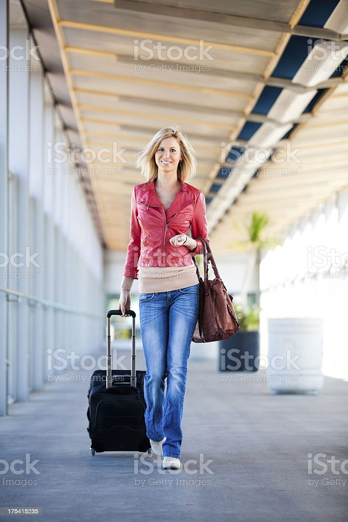 Beautiful young woman in an airport with a suitcase. royalty-free stock photo