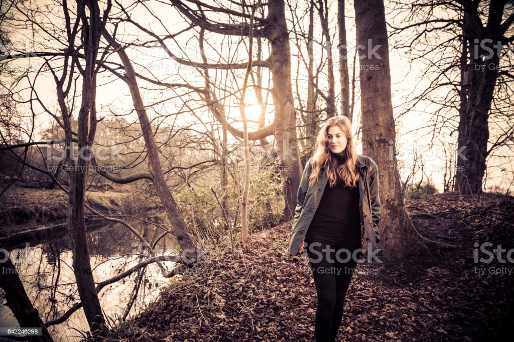 Beautiful young woman in black walking by a river stock photo