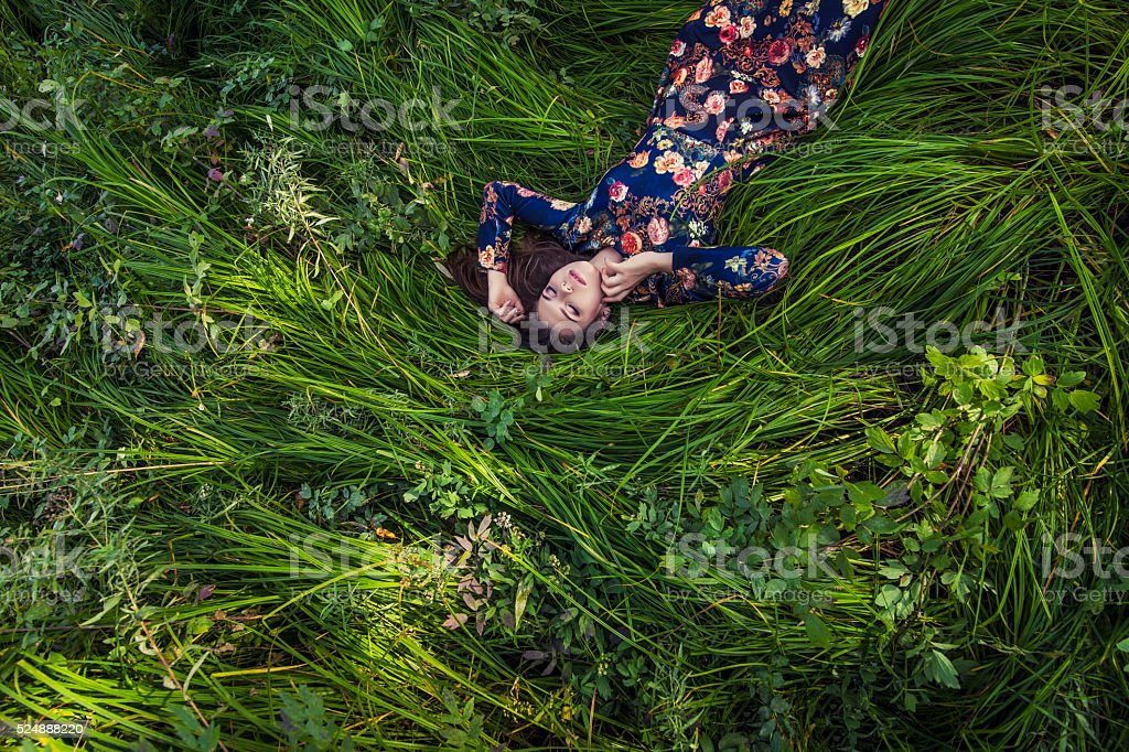 Beautiful young woman in dress lying in the grass stock photo