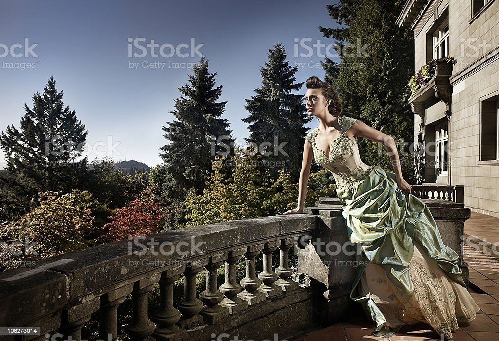 Beautiful Young Woman in Evening Gown on Mansion Balcony, Copyspace stock photo
