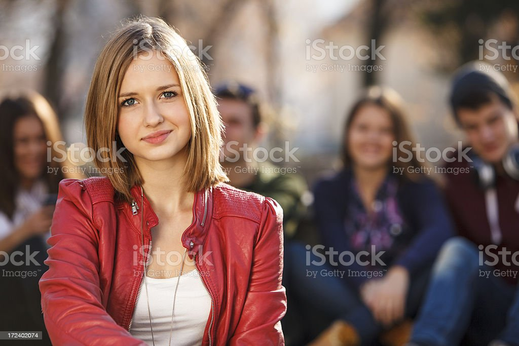 Beautiful young woman in front of her friends royalty-free stock photo
