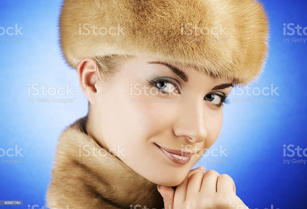 Beautiful young woman in fur cap royalty-free stock photo