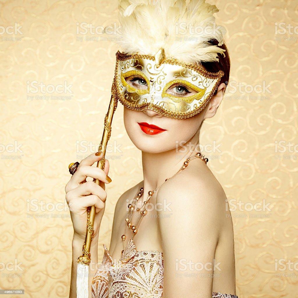 Beautiful young woman in mysterious golden Venetian mask stock photo
