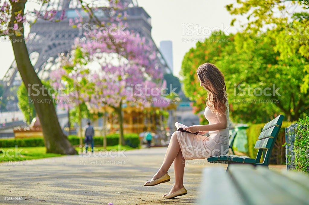 Beautiful young woman in Paris, reading a book stock photo
