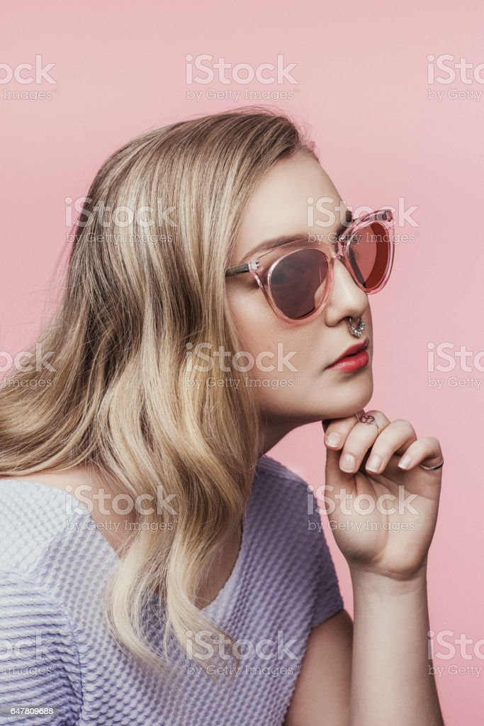 Beautiful young woman in pink sunglasses stock photo