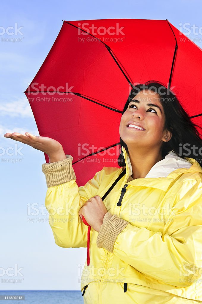 Beautiful young woman in raincoat with umbrella checking for rain royalty-free stock photo