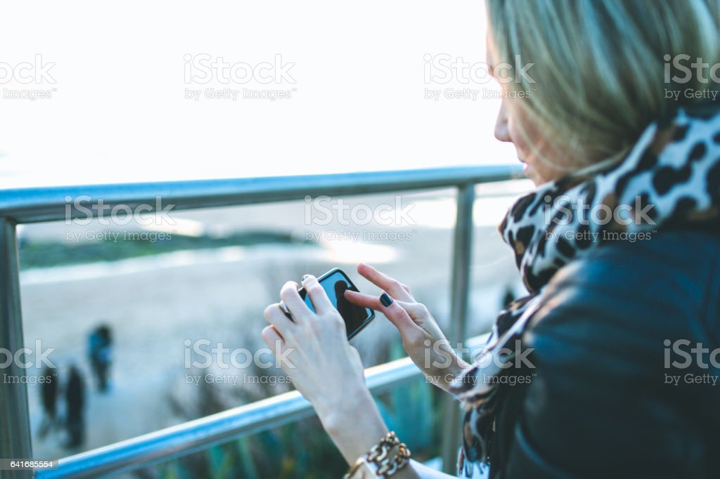 Beautiful young woman in real life using smartphone stock photo