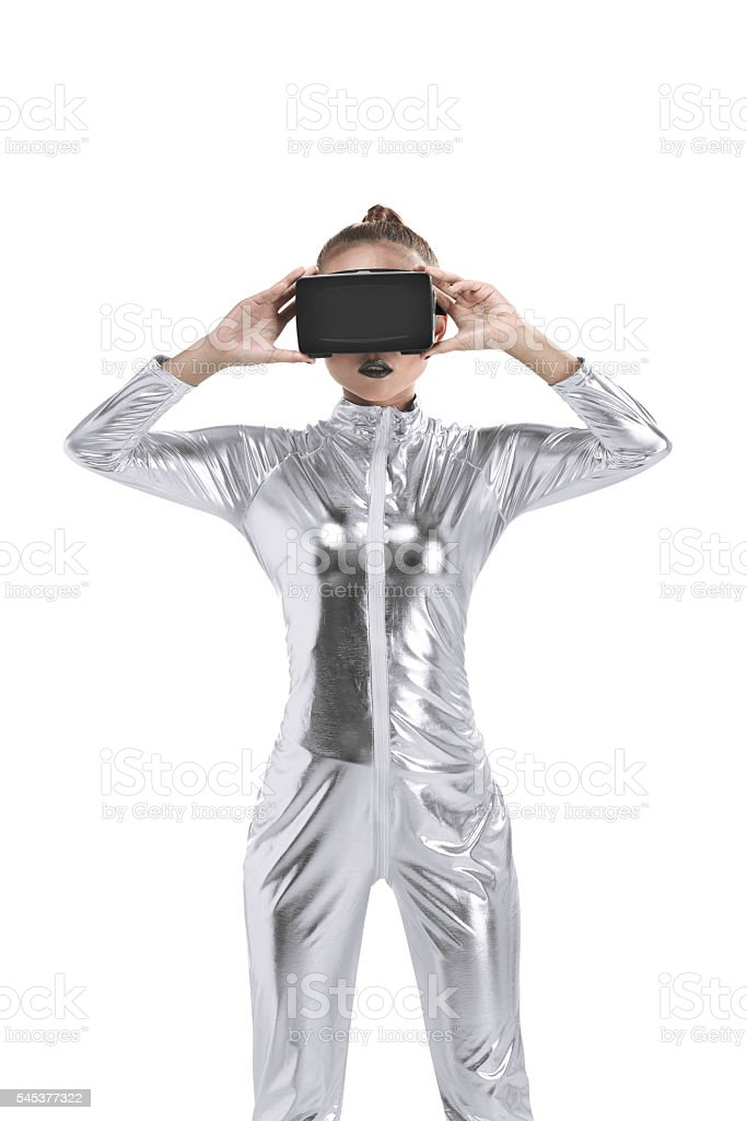 Beautiful young woman in silver latex costume and VR headset stock photo