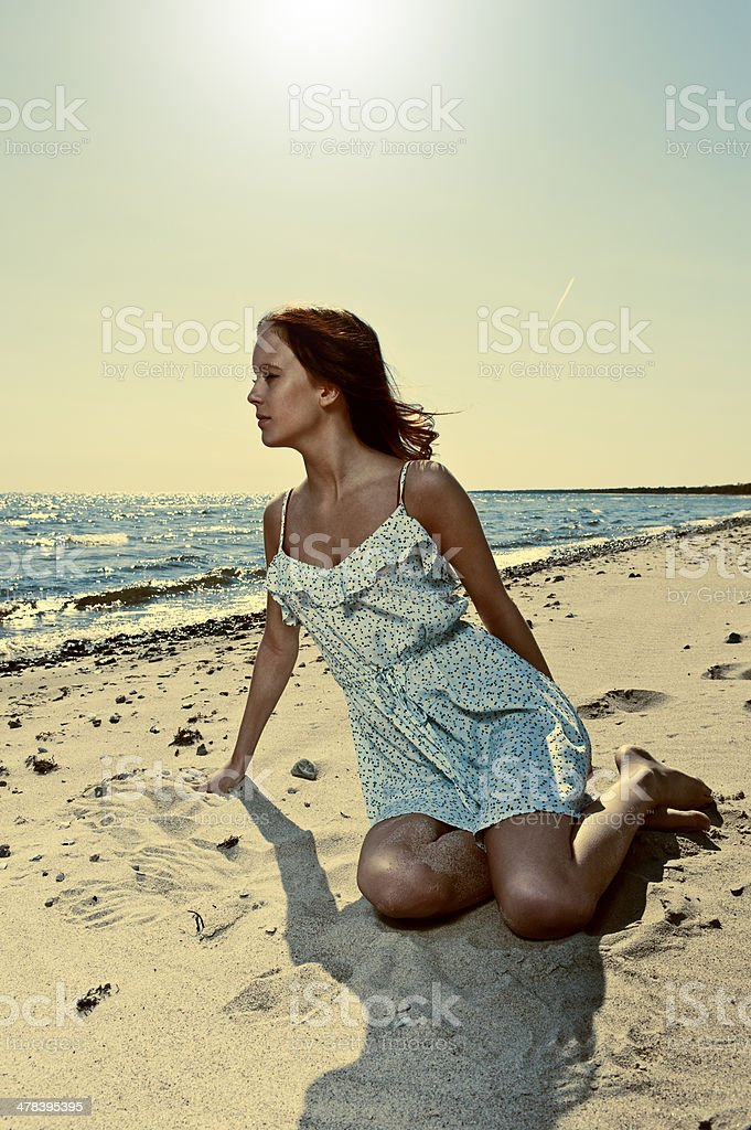 Beautiful young woman in summer dress sitting on the beach royalty-free stock photo