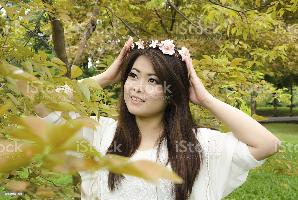 beautiful young woman in the park with her flower chaplet. royalty-free stock photo