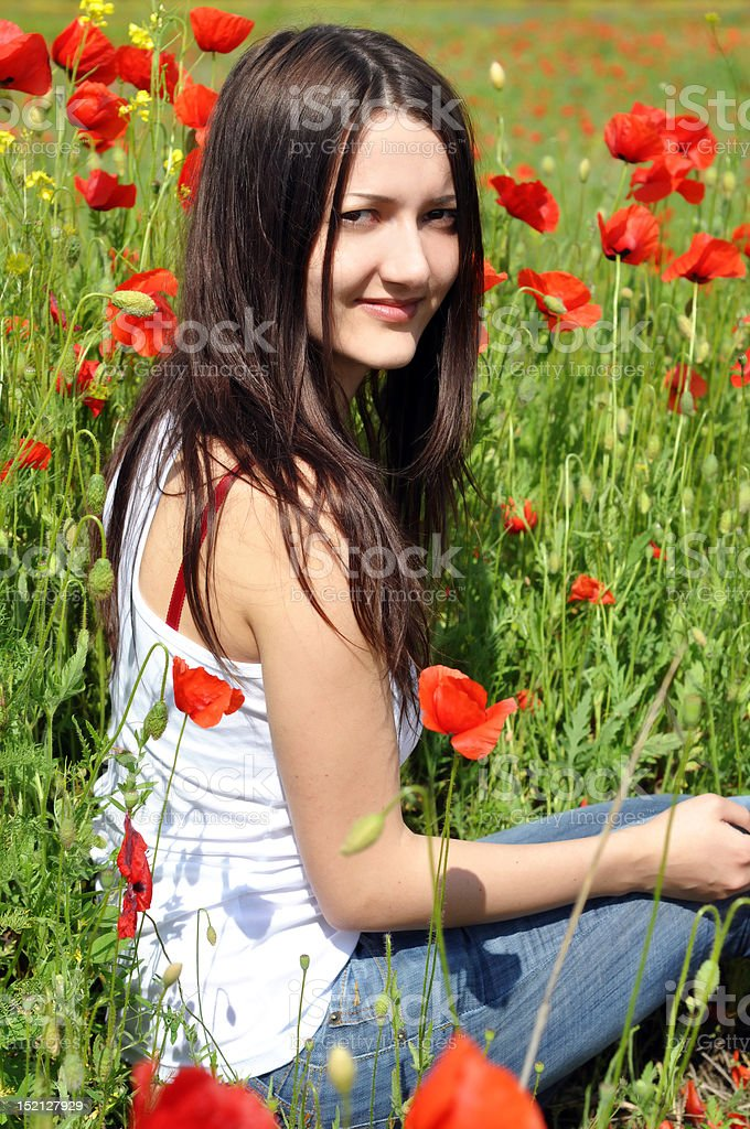 Beautiful young woman in the poppies stock photo