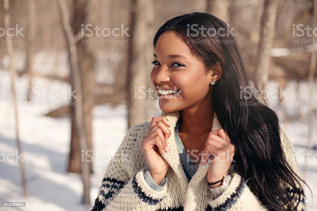 Beautiful young woman in the snow in winter stock photo