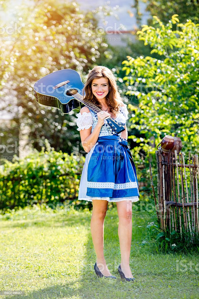 Beautiful young woman in traditional bavarian dress holding guit stock photo