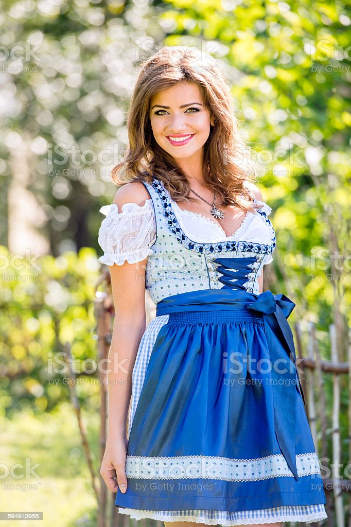 Beautiful young woman in traditional bavarian dress in park stock photo