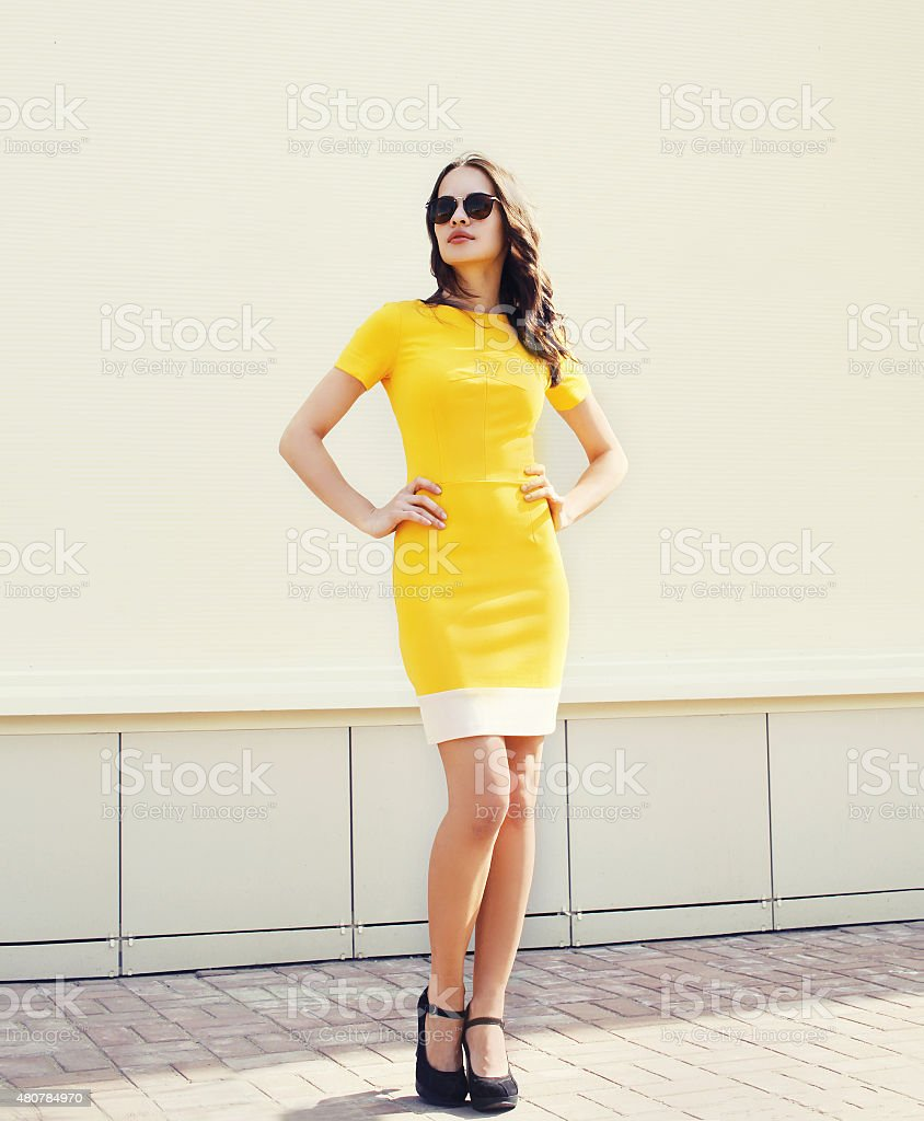 Beautiful young woman in yellow dress and black sunglasses posin stock photo
