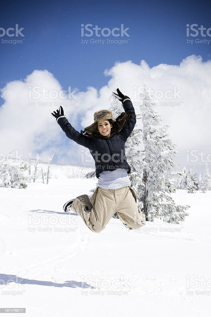 Beautiful Young Woman Jumping in Air on Snow Covered Mountain royalty-free stock photo
