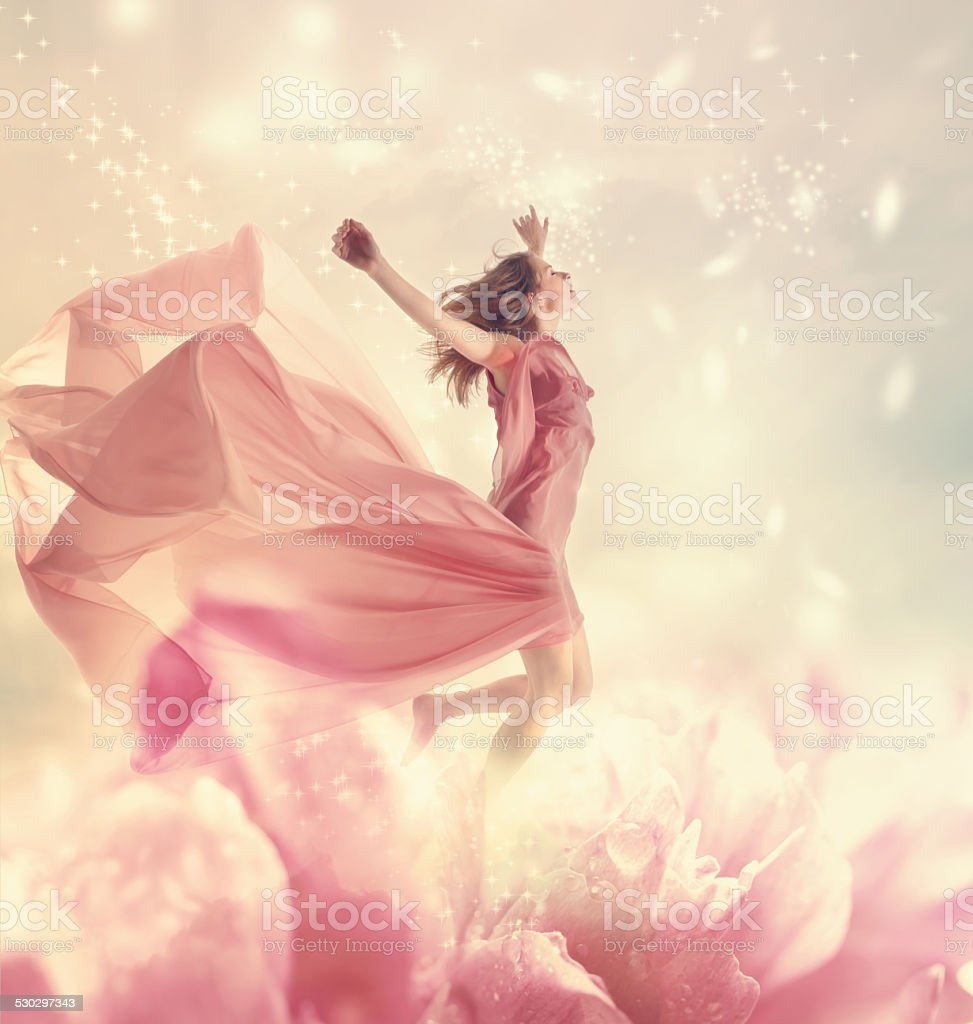 Beautiful young woman jumping on giant flower stock photo