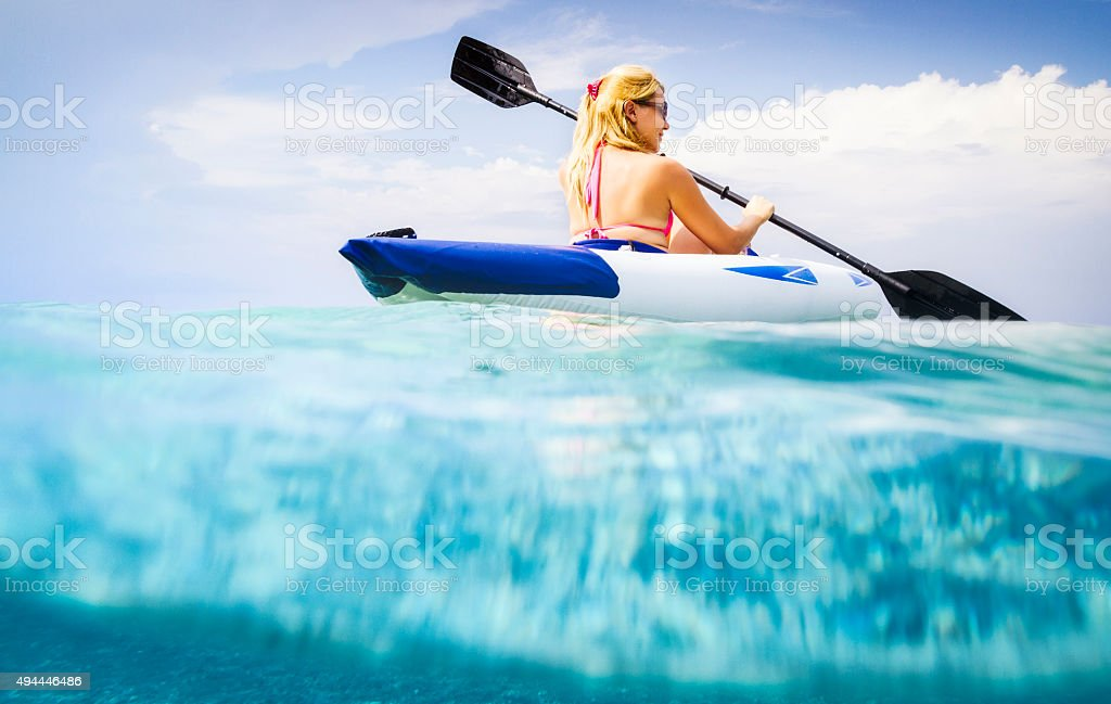 Beautiful young woman kayaking on sea with underwater view stock photo