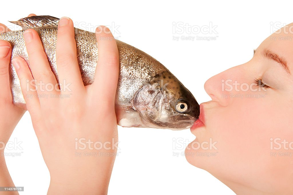 Beautiful young woman kissing a fish stock photo