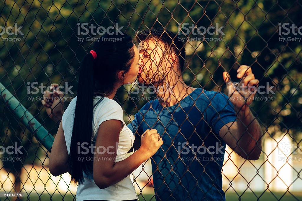 Beautiful young woman kissing handsome man through wire fence stock photo