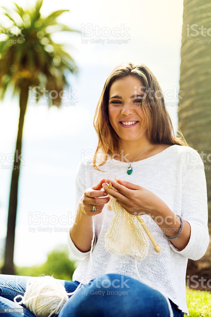 Beautiful young woman knitting in a park stock photo