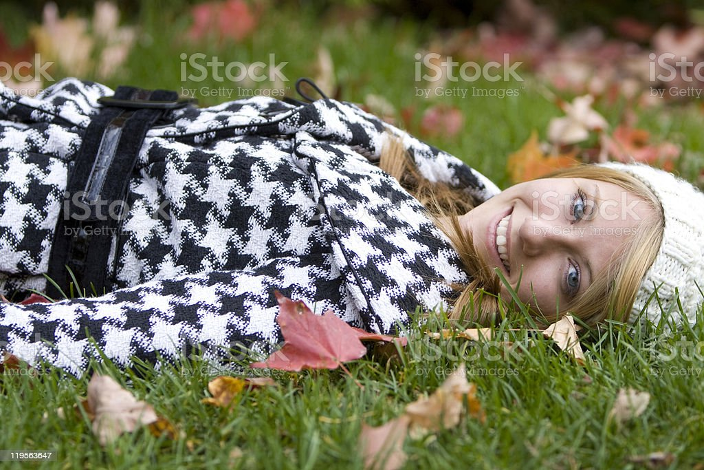 Beautiful young woman laying in Autumn leaves stock photo