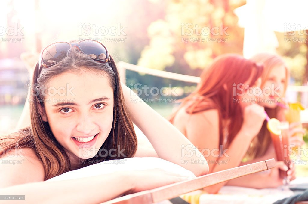 Beautiful Young Woman Laying On Sun Lounger Looking At Camera stock photo